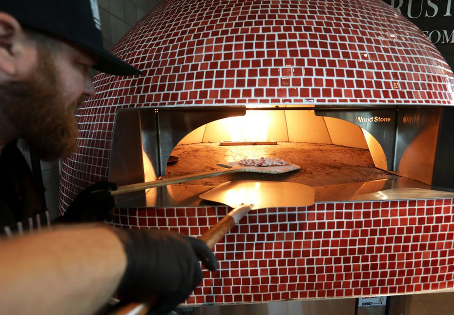 Micah Long makes a fig and prosciutto pizza at Rustic Flats, a food stand inside Urban8 in The Colony.