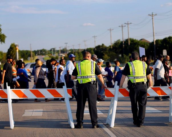 McKinney police watch as protesters march through the intersection of Alma Rd. and Silverado Trail after leaving Joyce Kelley Comstock Elementary, Monday June 8, 2015, for the Craig Ranch pool where McKinney Police Cpl.