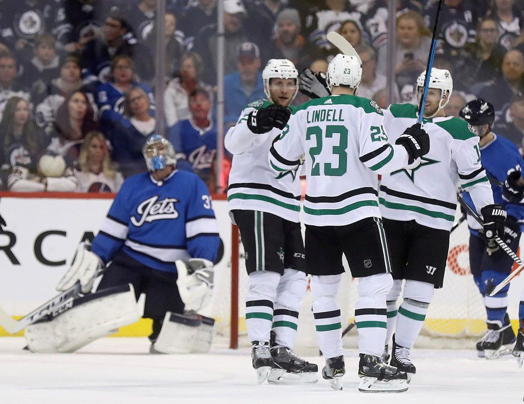 The Dallas Stars' celebrate after a goal by Esa Lindell (23) on Winnipeg Jets' goaltender Connor Hellebuyck (37) during the second period of an NHL hockey game Monday, March 25, 2019, in Winnipeg, Manitoba. (Trevor Hagan/The Canadian Press via AP)