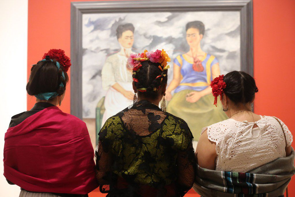 "Three Frida Kahlo lookalikes stand in front of the artist's 1939 work, 'The Two Fridas,' at the Dallas Museum of Art during the exhibit ""Mexico 1900-1950: Diego Rivera, Frida Kahlo, Jose Clemente Orozco and the Avant-Garde."""