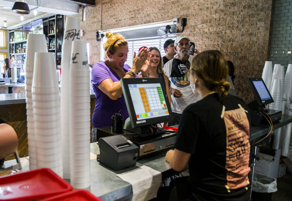 Emily McLaughlin applauds as she steps up to the register as the first customer at Heim Barbecue's new location on Saturday, August 6, 2016 on W. Magnolia Ave. in Fort Worth. McLaughlin, Cindy Podner and Jeff Knipper waited in line over night.