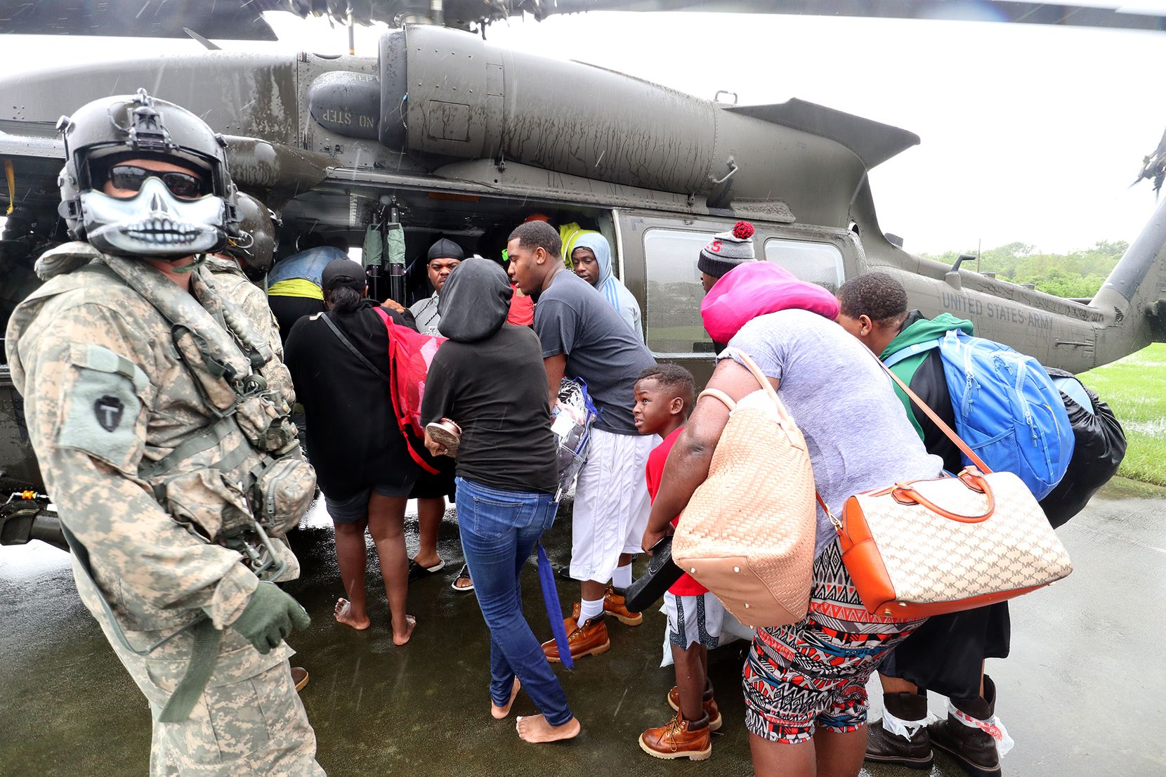 Victims from flooding from Harvey, board a waiting National Guard Black Hawk helicopter, on the basketball court of Valley View apartments, in Port Arthur Texas, August 30, 2017.