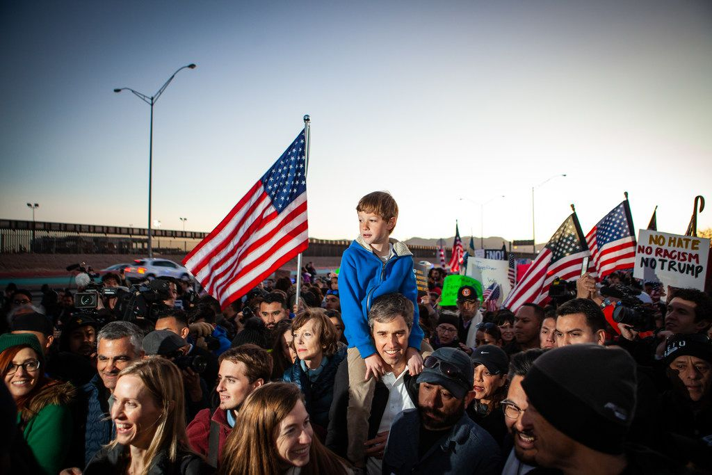 Beto O'Rourke carries his son Henry on his shoulders in El Paso as they march along the U.S.-Mexico border in protest of President Donald Trump's proposed border wall.