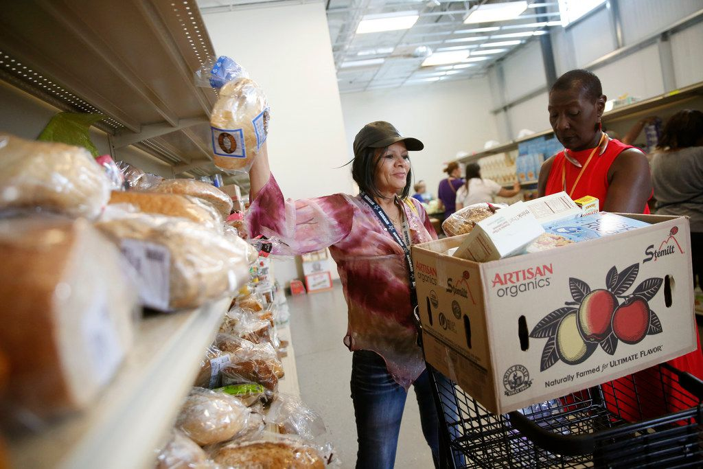 Valerie Clark with AARP (right) guides client Marcia Harrison as she picks out groceries at the CitySquare food pantry in Dallas on Wednesday, June 13, 2018. (Rose Baca/The Dallas Morning News)