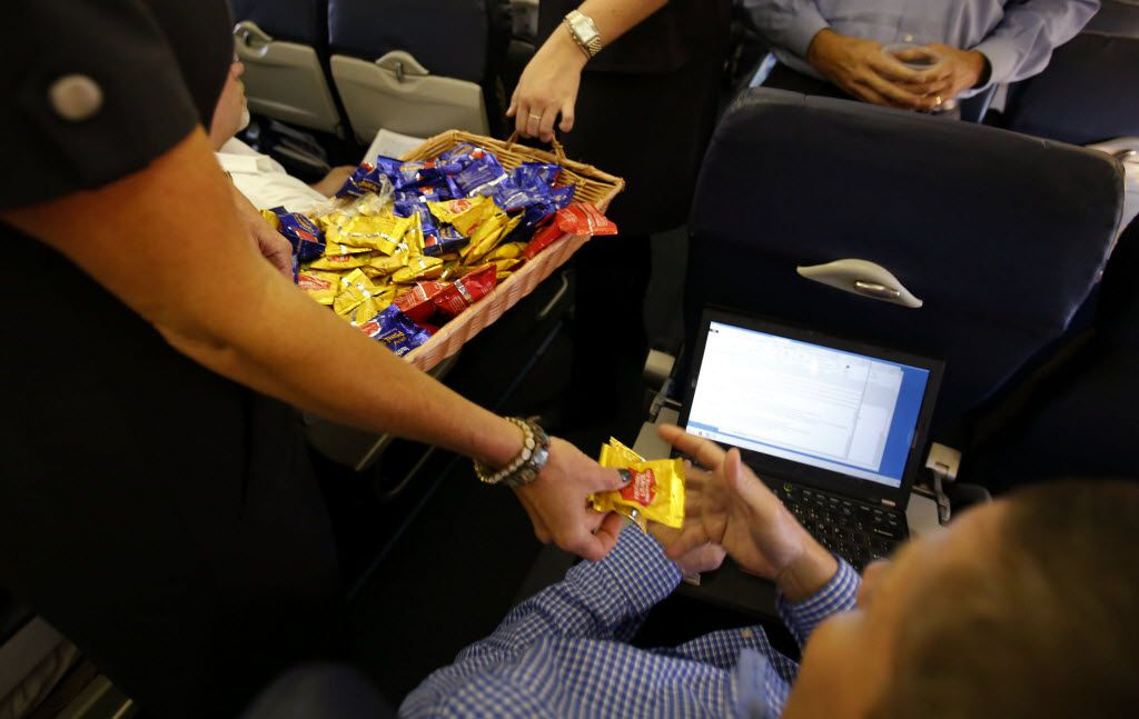 Southwest Airlines' Jenni Heikkinen hands out peanuts to passengers on Southwest Airlines No. 1013 to Denver in October, 2014. (Vernon Bryant/The Dallas Morning News)