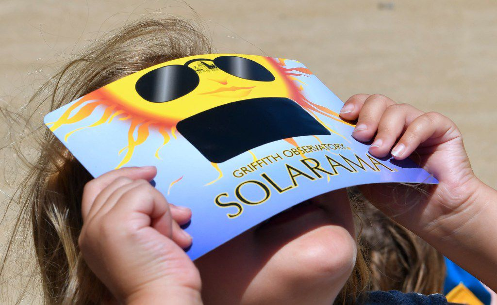 A child uses solar eclipse viewing glasses to look at the sun during the Solar Eclipse Festival at the California Science Center in Los Angeles, California on August 19, 2017, two days before The Solar Eclipse on Monday August 21. FREDERIC J. BROWN/AFP/Getty Images
