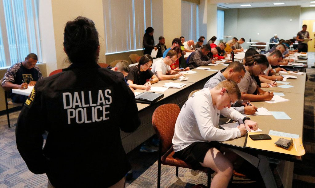 Dallas Police Senior Corporal Patricia A. San Martino, left, watches as applicants fill out paper work while applying for jobs as police officers at Jack Evans Police Headquarters in Dallas on Thursday, Sept. 7. About 80 candidates are applying to be Dallas police officers.
