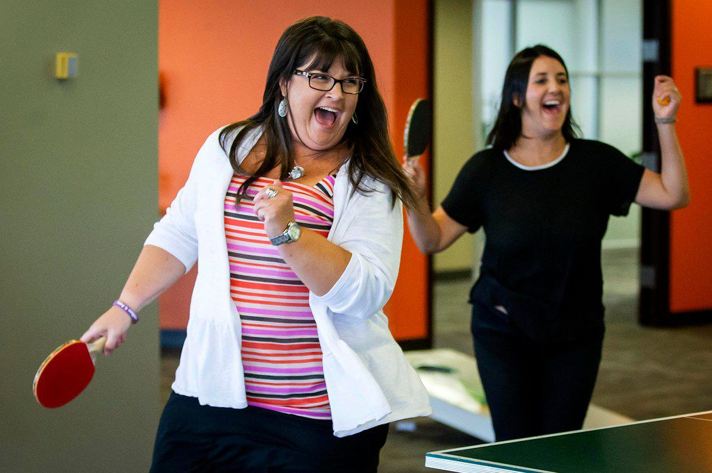Jeana Long (left) and Renee Greene celebrate making a point in a double table tennis game during a party celebrating the month's employee birthdays at Systemware in Addison.