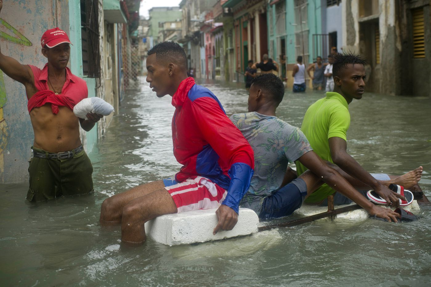 Residents float down a flooded street in Havana, Cuba atop a large piece of styrofoam, after the passing of Hurricane Irma in Cuba, Sunday, Sept. 10, 2017. The powerful storm ripped roofs off houses, collapsed buildings and flooded hundreds of miles of coastline after cutting a trail of destruction across the Caribbean.