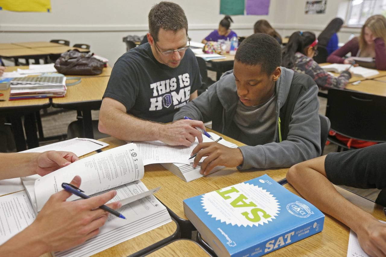 Teacher Wes Dennis helped Andrew Mburia during an SAT prep class at Independence High School in Frisco last month. New legislation will immediately exempt thousands of students from the stricter graduation requirements.