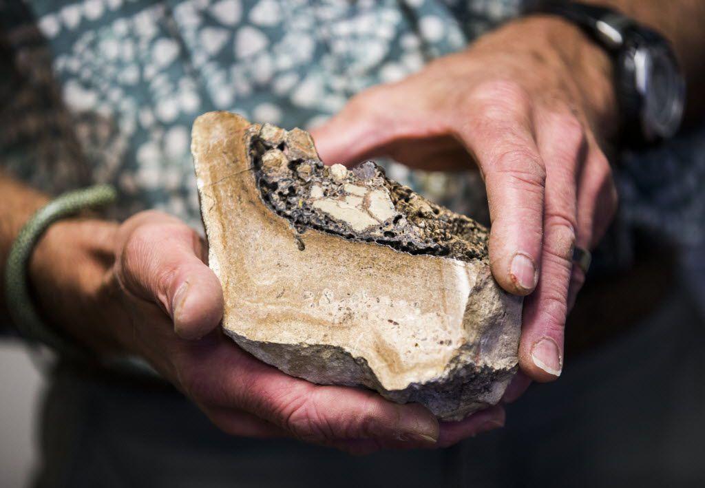John Geissman, UTD professor of geosciences, holds a rock donated by John Tackle.