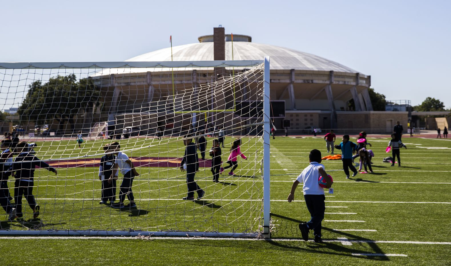 Burnet, Cigarroa and Pershing Elementary School students play on the track and football field outside Alfred J. Loos Athletic Complex, where they are temporarily holding classes, on Wednesday, October 23, 2019 in Dallas. The schools were damaged as multiple tornadoes ripped through the DFW area on Sunday night. (Ashley Landis/The Dallas Morning News)