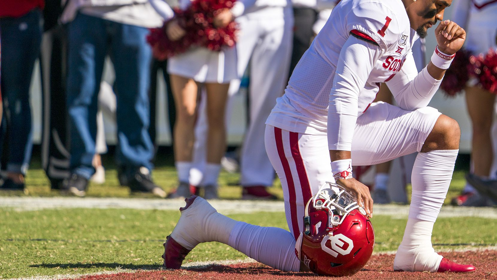 Oklahoma quarterback Jalen Hurts (1) prays on the field before an NCAA football game between Texas and Oklahoma at the Cotton Bowl on Saturday, Oct. 12, 2019, in Dallas.