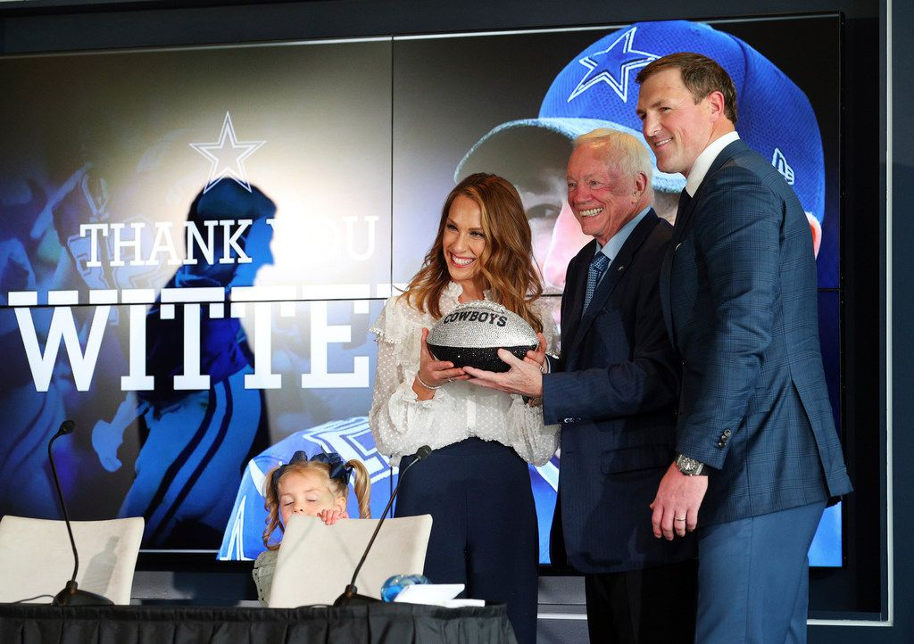 Retiring Dallas Cowboys tight end Jason Witten, right and his wife Michelle, left, are presented with a crystal covered football by team owner Jerry Jones, center, after a press conference at team's training facility and headquarters where Witten announced his retirement from the NFL, Thursday, May 3, 2018, in Frisco, Texas. The Witten's daughter Hadley, bottom, looks on. (AP Photo/Richard W. Rodriguez)