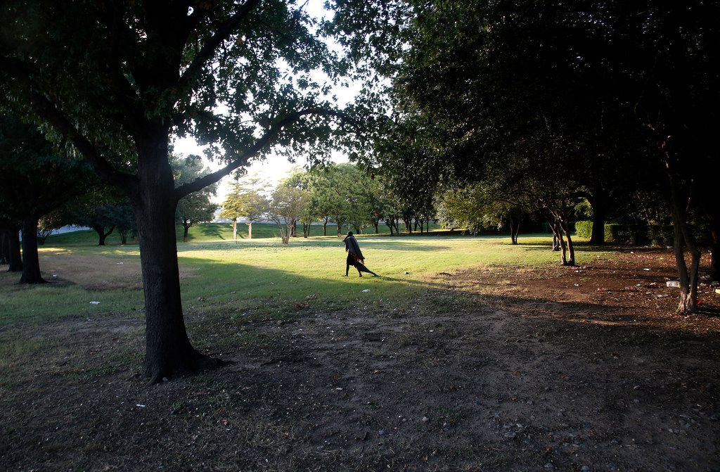 A homeless man drags a blanket in Martyrs Park in Dallas on Thursday, Oct. 5, 2017.