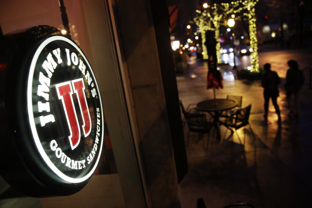 Pedestrians pass by a Jimmy John's sandwich shop, Friday, Jan. 2, 2015, in Atlanta. A lawsuit targeting the fast-food sandwich chain has put scrutiny on agreements banning low- and middle-wage workers from competing against their former employers. (AP Photo/David Goldman) 01052015xBIZ