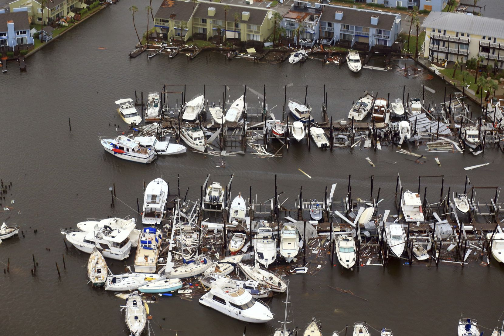 This aerial photo shows damaged boats along a dock in the wake of Hurricane Harvey, Monday, Aug. 28, 2017, in Corpus Christi, Texas. Harvey hit the coast as a Category 4 hurricane. (Gabe Hernandez/Corpus Christi Caller-Times via AP)