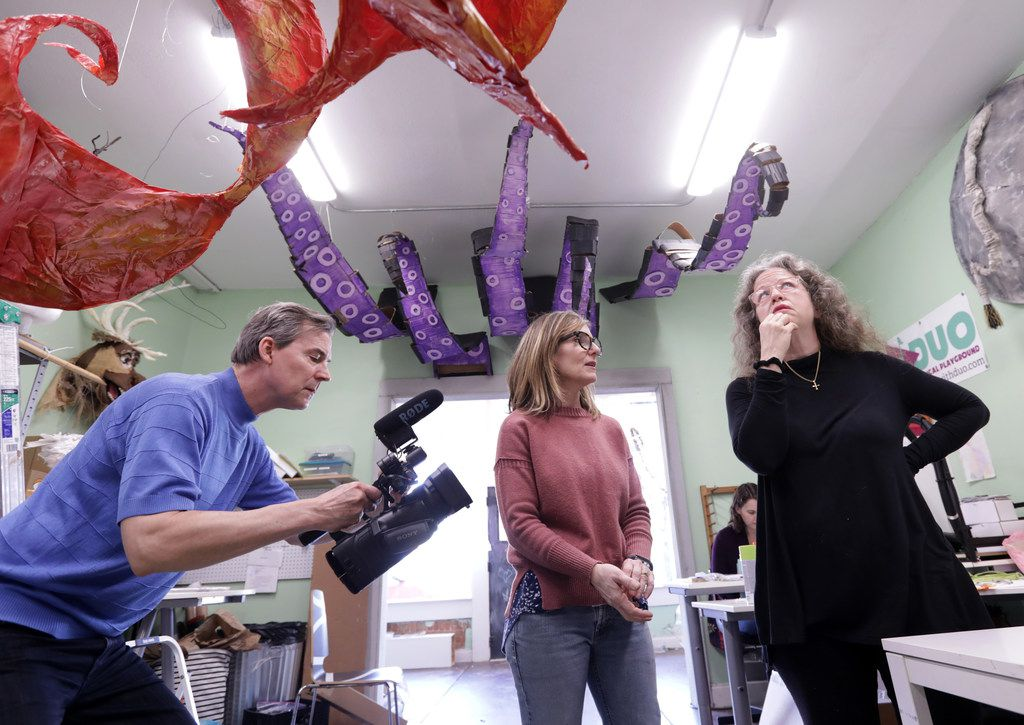 Scott Browning, left, films Melissa Patrello and Anne Royer as they discuss a sculptural art installation with at Melissa's studio space in McKinney.