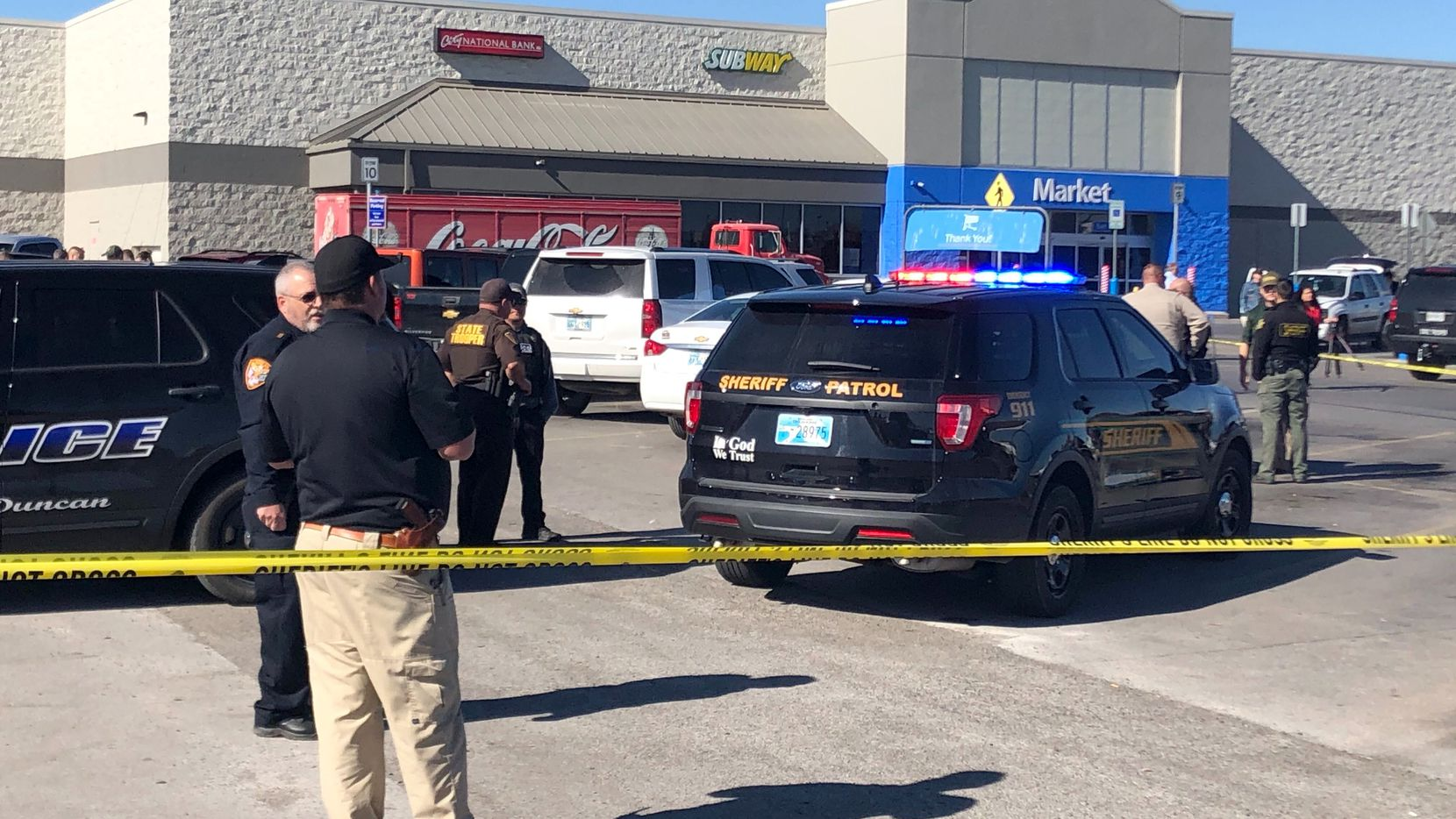 Law enforcement personnel investigate outside a Walmart where two men and a woman were fatally in Duncan, Okla.