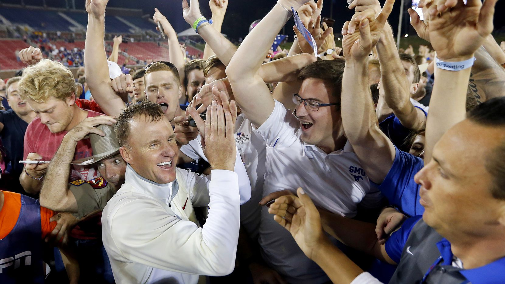 Southern Methodist Mustangs head coach Chad Morris celebrates his upset win over the Houston Cougars with students and fans at Gerald J. Ford Stadium in University Park, Texas, Saturday, October 22, 2016. SMU upset Houston, 38-16.