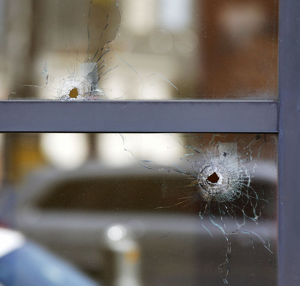 Two bullet holes in the windows of El Centro College are seen at the scene where the five police officers were killed in the line of duty in Thursday night's deadly shooting on Elm Street in downtown Dallas, Tuesday, July 12, 2016.