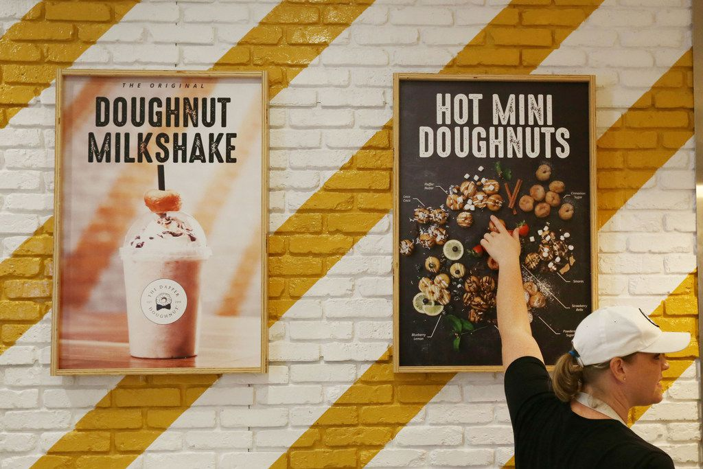 Brooke Sanchez explains the menu to customers at The Dapper Doughnut in the Galleria Dallas mall in Dallas Monday May 28, 2018. Owners Brooke Sanchez and Leo Sanchez opened the store four weeks ago. They own the 14th franchise location of The Dapper Doughnut. All doughnuts are made to order. (Andy Jacobsohn/The Dallas Morning News)