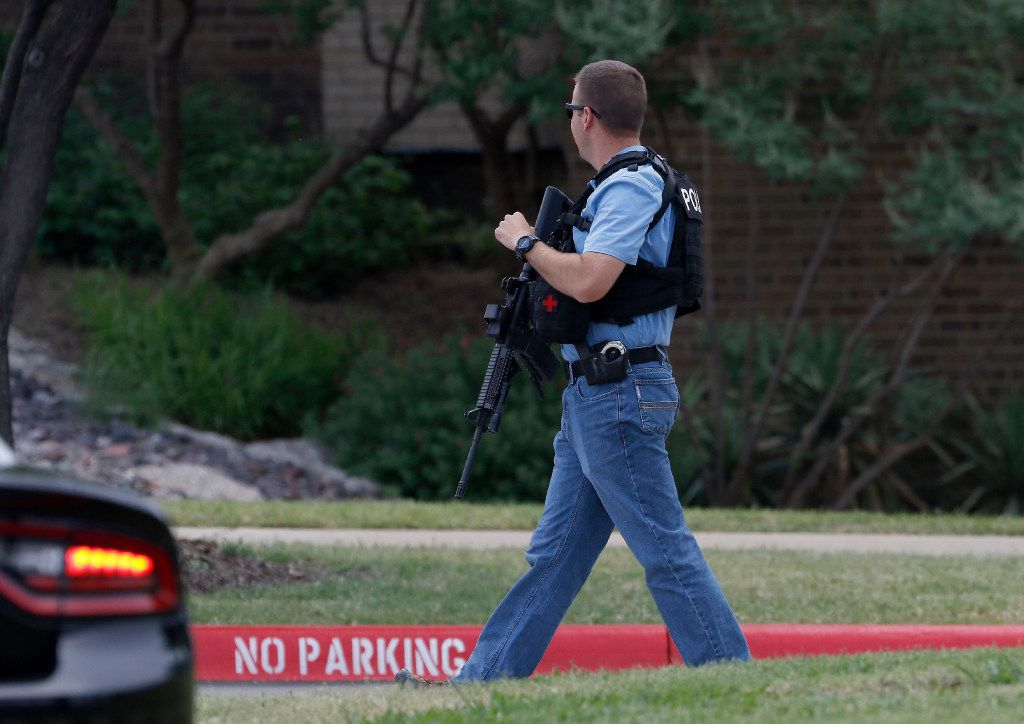 An Irving police officer works at the shooting scene.