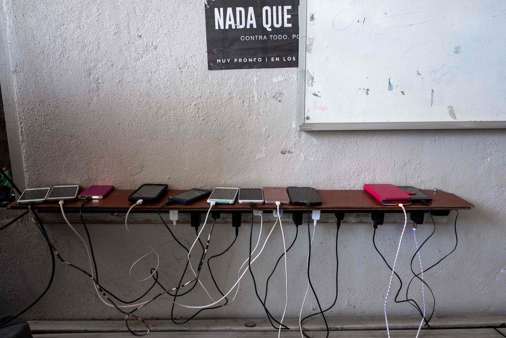 TOPSHOT - Cellphones of migrants seeking for asylum in the United States are seen charging in Juventud 2000 migrant shelter in Tijuana, on March 5, 2019. - According to the US Customs and Border Protection, statistics observed more than a 300 percent increase in the number of family units apprehended compared to the same time period in 2018. (Photo by Guillermo Arias / AFP)GUILLERMO ARIAS/AFP/Getty Images