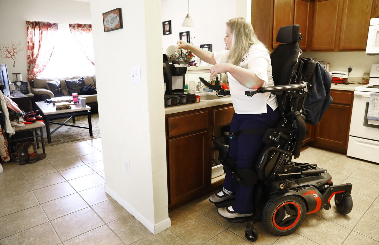 Jessica Lukefahr makes a mug of tea in her powered wheelchair with standing function. It took Lukefahr several years and a few court battles to eventually be given the chair, which allows her safety, independence and mobility. Her case exemplifies the arbitrary and unfair nature of how the state handles Medicaid appeals of denied care.