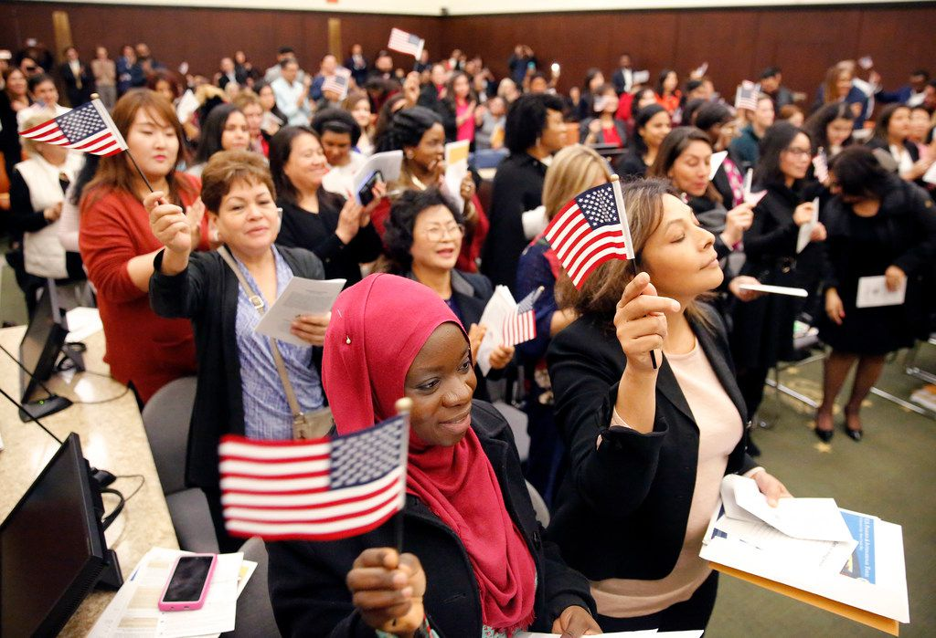 Fatimah Oritola of Nigeria (foreground) of Nigeria and others wave U.S. flags after reciting the oath of allegiance led by US Chief District Judge Barbara Lynn during a naturalization ceremony at the Earle Cabell Federal Building in Dallas Dec. 19. (Tom Fox/The Dallas Morning News)