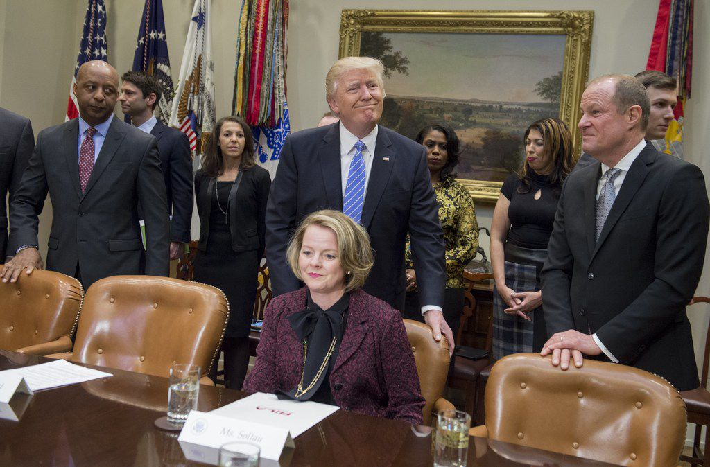 President Donald Trump pushed in the chair for Jill Soltau, then CEO of Jo-Ann stores, alongside Art Peck (right), CEO of Gap Inc., and Marvin Ellison (left), former CEO of J. C. Penney, as Trump arrives to meet with retail industry leaders in the Roosevelt Room of the White House in Washington, D.C., on Feb. 15, 2017.
