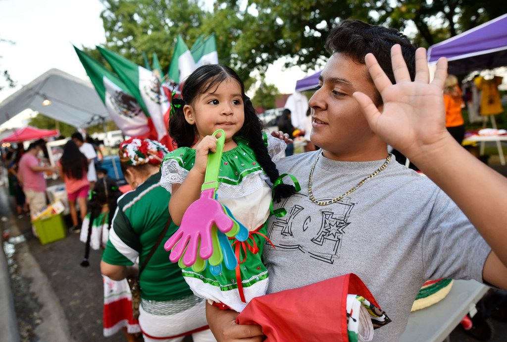Michelle Ruano is held by her cousin Christian Soriano as they listen to music during the Mexican Independence Day celebration, Fiestas Patrias, at the Latino Cultural Center in Dallas.