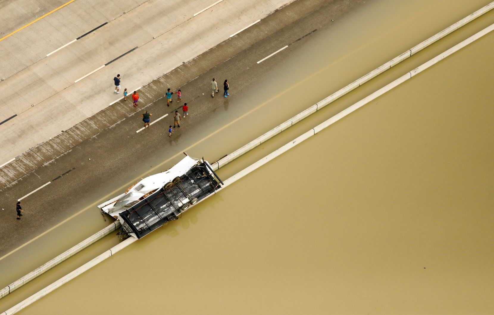 People gather along flooded Interstate 69 to see a recreational vehicle overturned in the rainwater left from Hurricane Harvey in Humble, Texas, Wednesday, August 30, 2017.