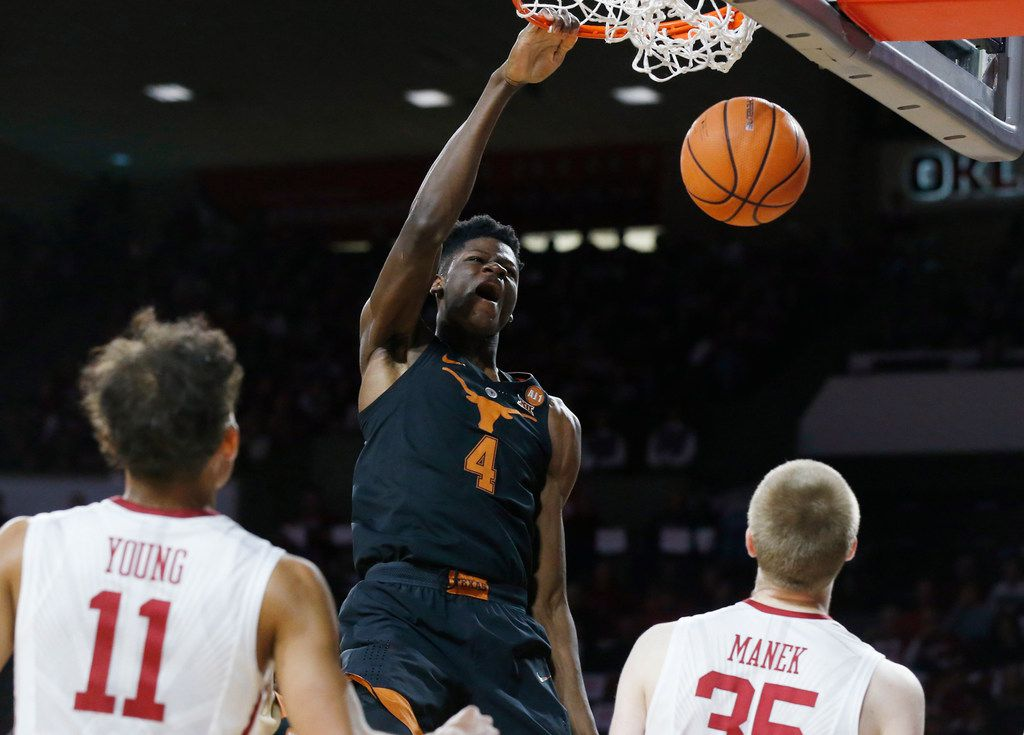 Texas forward Mohamed Bamba (4) dunks in front of Oklahoma guard Trae Young (11) and forward Brady Manek (35) in the first half of an NCAA college basketball game, in Norman, Okla.