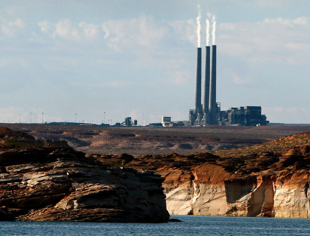 FILE - This Sept. 4, 2011, file photo shows the main plant facility at the Navajo Generating Station, as seen from Lake Powell in Page, Ariz. The possible shutdown of the northern Arizona coal-fired power plant that provides hundreds of jobs is drawing opposition from two Native American tribes and a state utility regulator.(AP Photo/Ross D. Franklin, File)