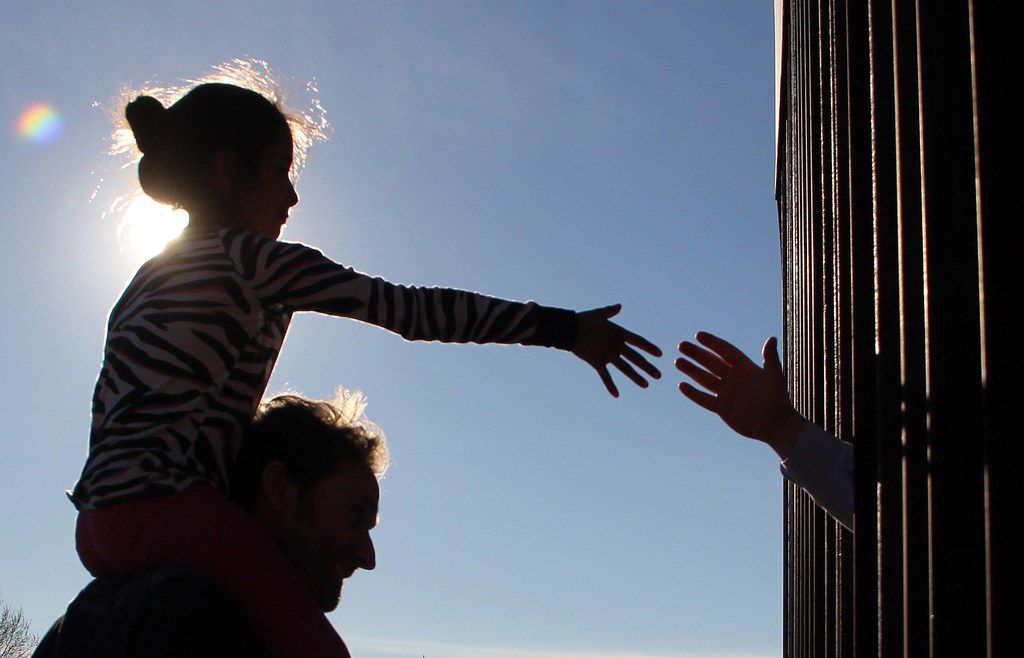 A girl from Anapra, a neighborhood on the outskirts of Ciudad Juarez in Mexico, touches hands with a person in the United States through the border fence during a prayer with priests and bishops from both countries on February 26, 2019.
