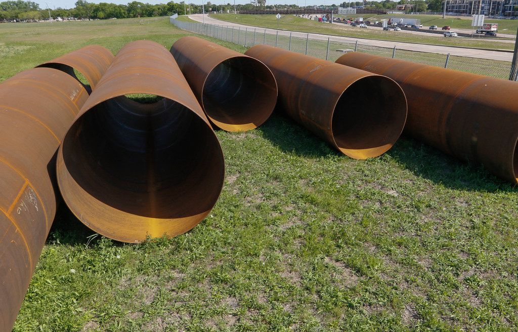 Large pipes lay on undeveloped land at Skillman Street and LBJ Freeway in Dallas on April 20, 2018. In the background is eastbound traffic on LBJ Freeway. (Ron Baselice/The Dallas Morning News)