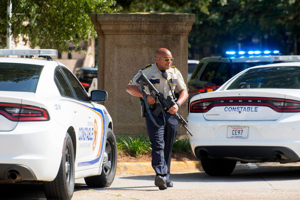 A Baton Rouge City Constable's Office officer with a weapon walks near two LSU police vehicles and Constable's Office units parked between the LSU Student Union and Coates Hall during the investigation of a possible armed intruder in Coates Hall on Tuesday, Aug. 20, 2019.
