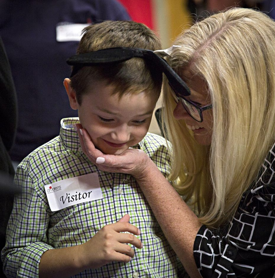 Cindy Krueger embraces her grandson, Harley Archibald, after the Children's Medical Center Dallas patient learned his Make-A-Wish was granted on Tuesday in Dallas.  (G.J. McCarthy/The Dallas Morning News)