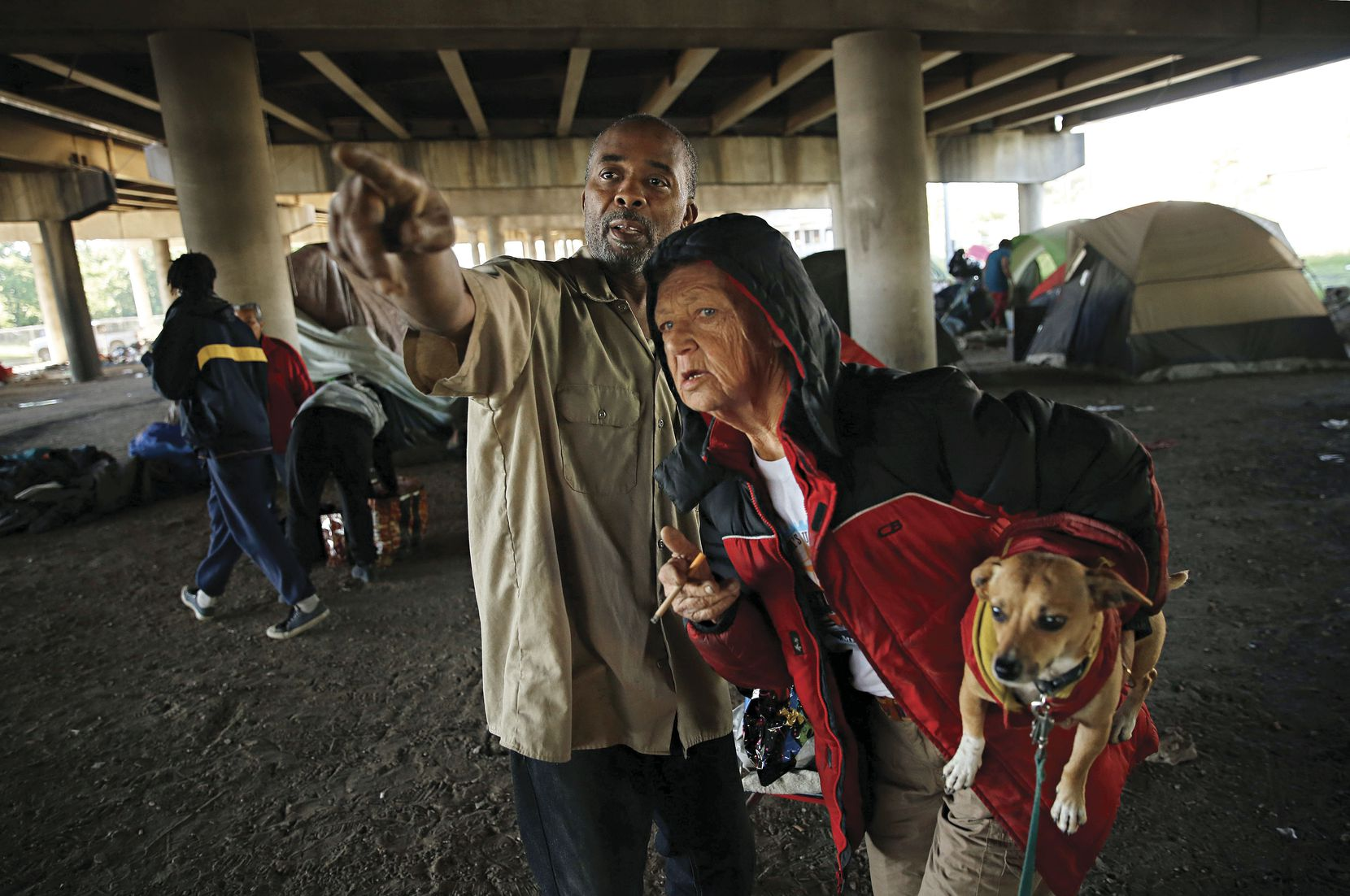 "As officials fenced off an area of Tent City to shut out those dwelling there, a man who calls himself ""Cut"" pointed the workers out to fellow Tent City resident Darlene Finley, on May 3."
