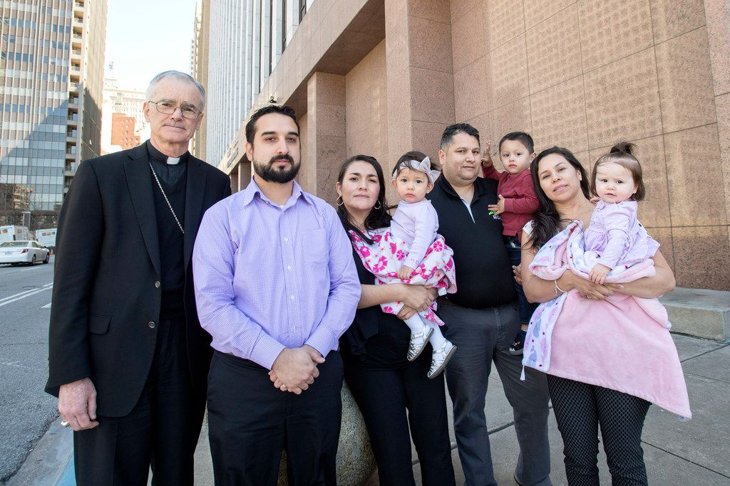 Lucia Mejia, wife of Adolfo Mejia (center), holds her 19-month-old daughter, Teresa Mejia, as she is surrounded by friends and supporters (from left) Auxiliary Bishop Greg Kelly; godfather to Teresa Mejia, Daniel Casiamano; friends Horacio and Maura Ortega, holding their son Emmanuel and daughter Genesis. They stand outside the Earle Cabell Federal Building before a court hearing for her husband.