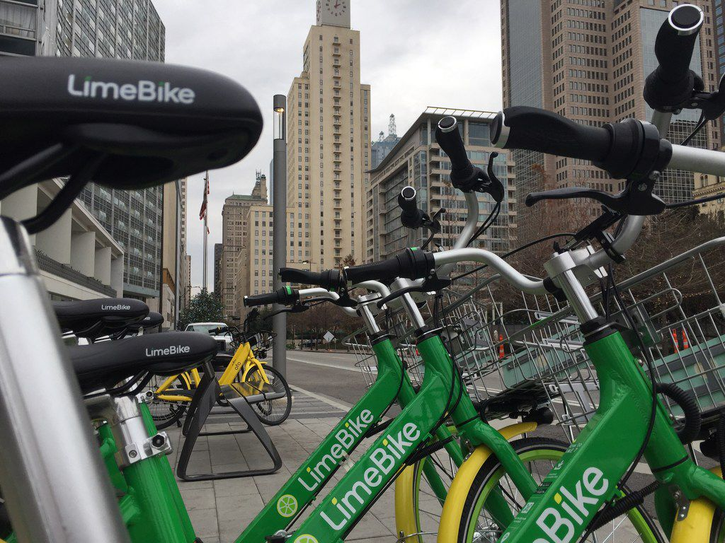 LimeBikes are parked on Commerce St in downtown Dallas, Texas on December 27, 2017.