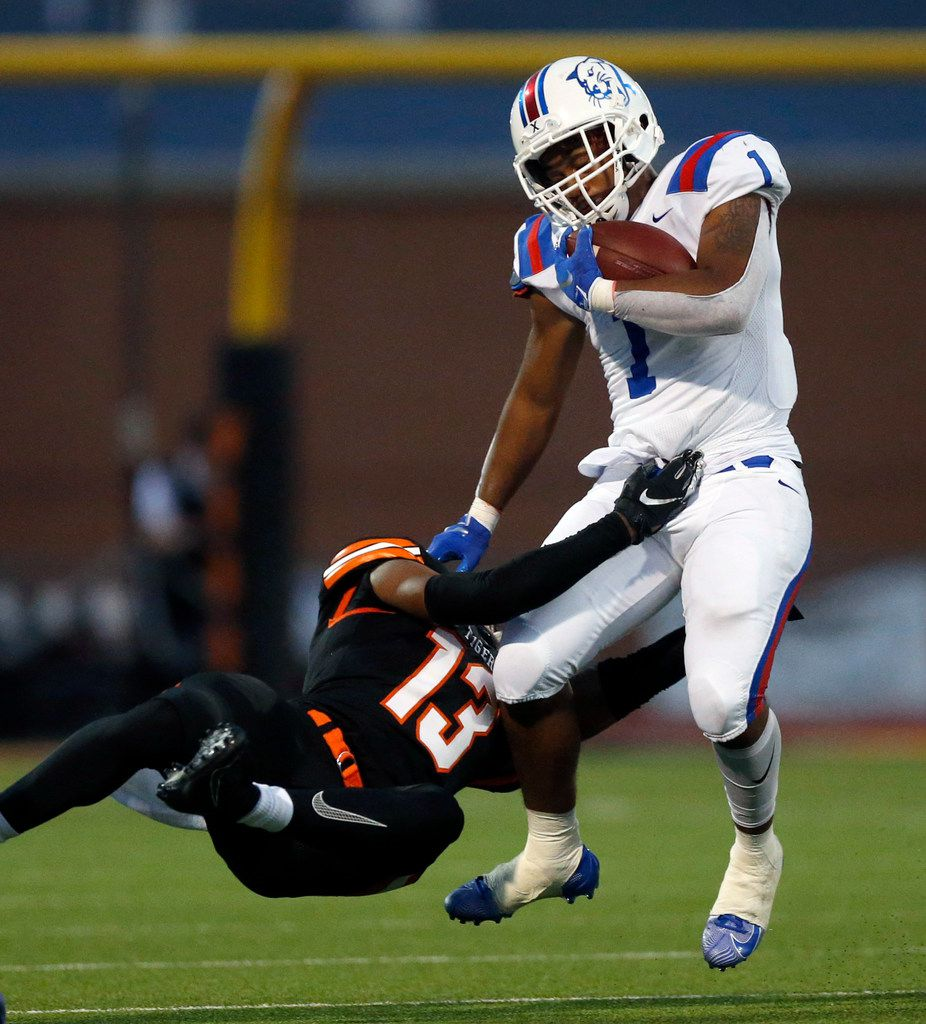 Duncanville running back Trysten Smith (1) is tackled by Lancaster defensive back Theron Stroops (13) during the first quarter at Beverly D. Humphrey Tiger Stadium in Lancaster Texas, Friday, August 30, 2019. (Tom Fox/The Dallas Morning News)