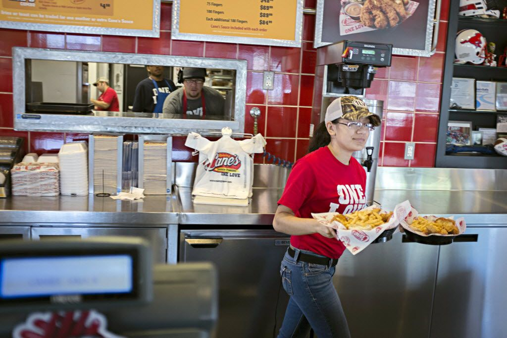 Marymar Gracia walks an order from the kitchen to a customer at a Raising Cane's Chicken Fingers restaurant in Dallas. Most customers get some version of this: chicken fingers and crinkle-cut fries.