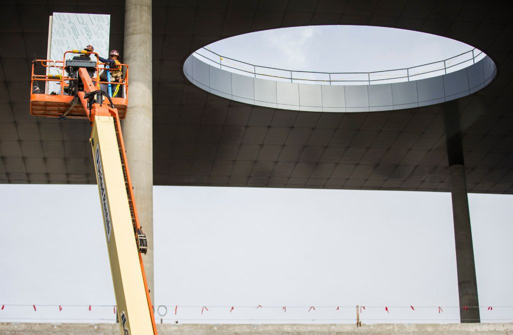 Construction workers move supplies near the front entrance of the future site of Toyota world headquarters on Thursday, October 13, 2016 in Plano, Texas. (Ashley Landis/The Dallas Morning News)
