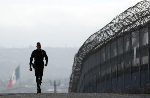 Un agente de la Patrulla Fronteriza camina al lado de la barda que separa Estados Unidos de Tijuana, México. Foto AP