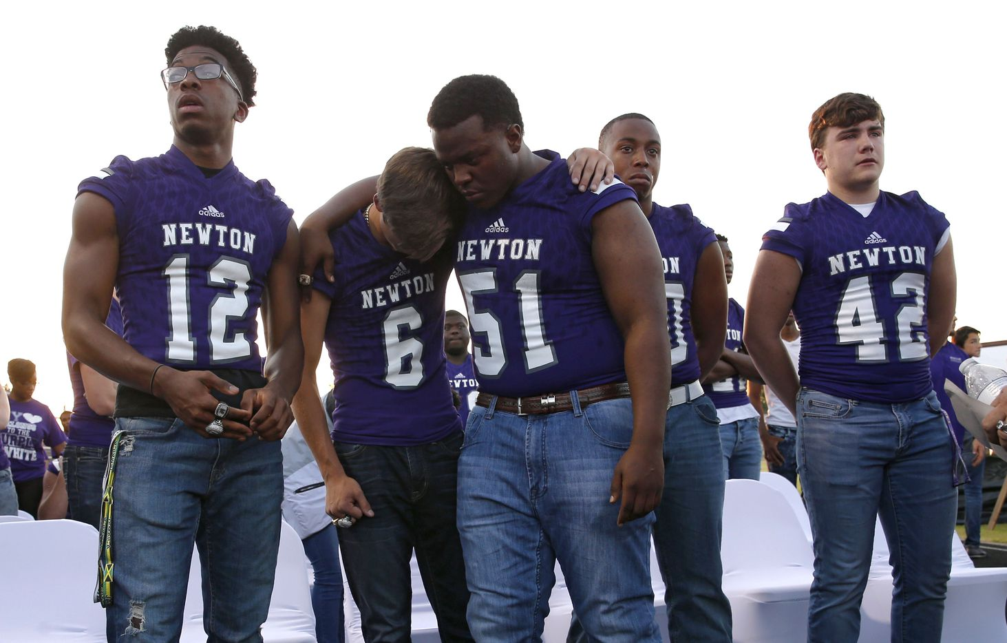 """Newton's Nate Williams (6) is consoled by teammate Avante Burnham (51) during the memorial service for Newton High School head football coach William Theodore """"W.T."""" Johnston at Curtis Barbay Field at Newton High School in Newton, Texas on Wednesday, May 15, 2019. Zach Gulley (12), Jamarion Samuel (50), Brice Westbrook (42) stand nearby. (Vernon Bryant/The Dallas Morning News)"""