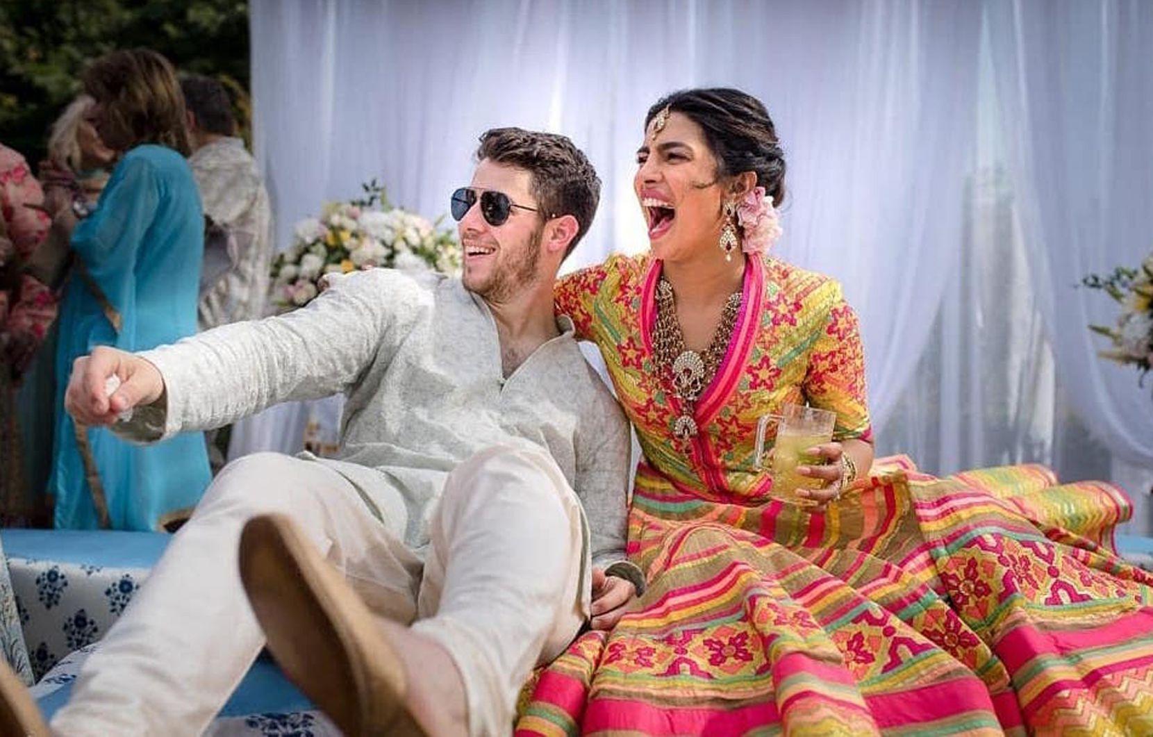 In this handout photo released by Raindrop Media, Bollywood actress Priyanka Chopra and Nick Jonas celebrate during a mehendi ceremony at Umaid Bhawan in Jodhpur, India.