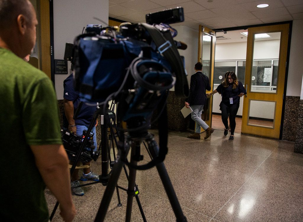Reporters walk in the hallway outside the central jury room where would-be jurors answered questionnaires to determine whether they will be chosen for the murder trial of Amber Guyger.