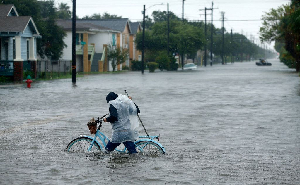 Monica Grant of Galveston pushes her bike through flooded streets near Broadway Ave.,Tuesday, August 29, 2017. The city of Galveston, Texas was flooded from punishing overnight rains from Tropical Storm Harvey which passed by the island, Tuesday.(Tom Fox/The Dallas Morning News)